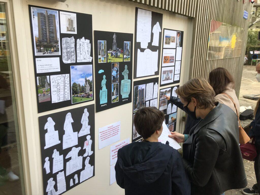 Ouders kijken naar kunstwerken van leerlingen van De Rivieren